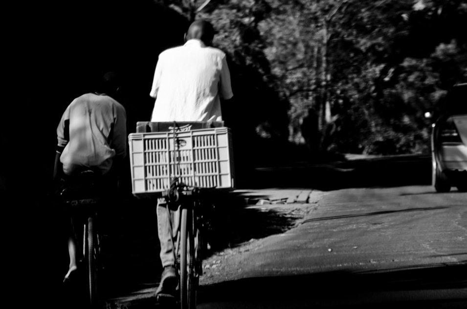 He is riding Bayi's bicycle as well as Bayi's wife.